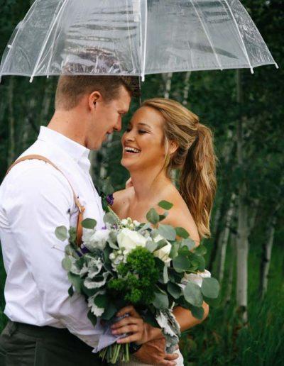 wedding couple smiling under umbrella