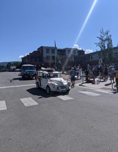 Old car with American Flags in parade.