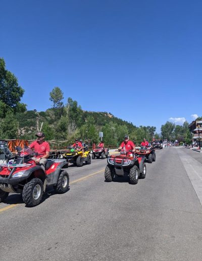 4-wheelers parading down street in parade.