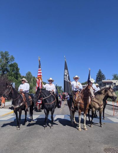 People on horses lined up in the 4th of July Parade.