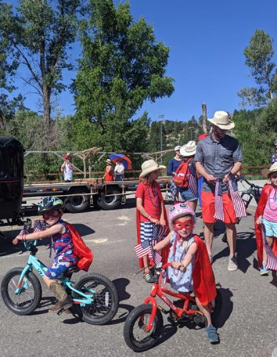 Kids dressed up with capes and masks on bikes for 4th of July Parade.