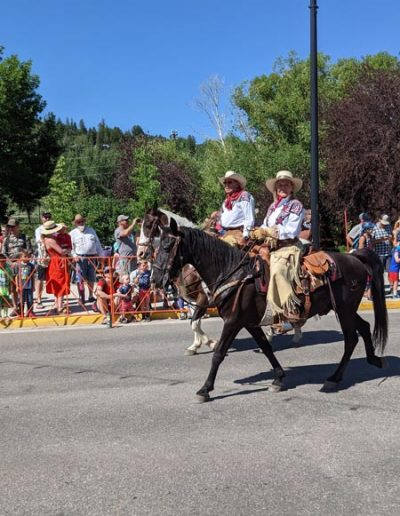 Cowboy and Cowgirl on horse in parade.
