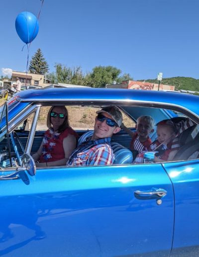 Blue and red balloons hung on blue car in 4th of July Parade