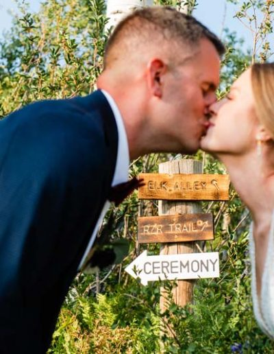 Blurred Bride and Groom kissing in foreground with signs in focus.