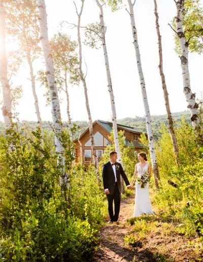 Bride and Groom in Aspen trees with house in the background.