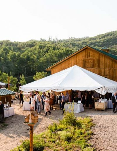 Barn with white tent and wedding guest.