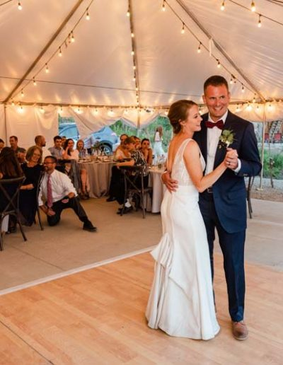 Bride and Groom on the dance floor with seated table guest watching.