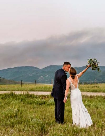 Bride and Groom kissing with mountains in the background.