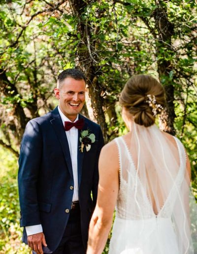Groom smiling at Bride during first look.