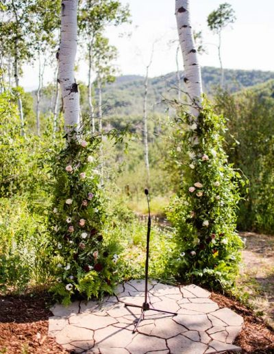 Two aspen trees wrapped in flowers to make archway.